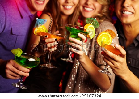 Young people having fun at a birthday party with cocktails