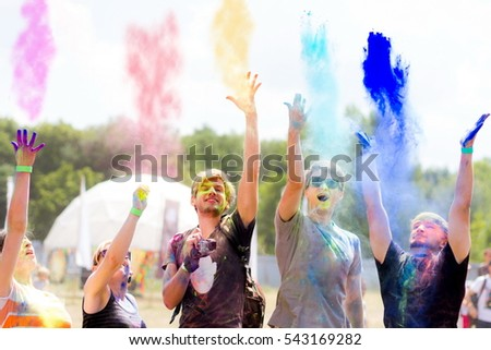 Young people having fun during Holi fest throwing colorful powder in the air