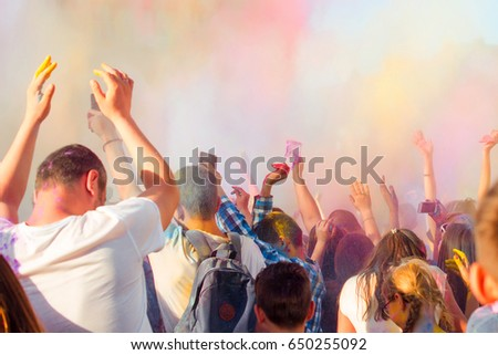 Young people having fun during Holifest, throwing colorful powder in air