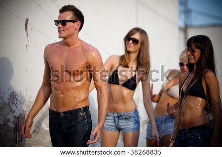 Young people having fun on summer vacation. Girl splashing boyfriend with water