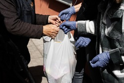Young people helping old woman with products. Hands in gloves, help during quarantine  through coronavirus infection. Social help and support. Volunteering. Taking care of loved ones. Charity.