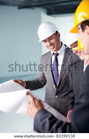 Young people in business suits and helmets on a construction site