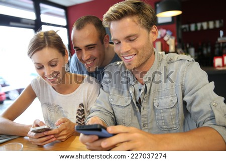 Young people in campus lounge connected on smartphone