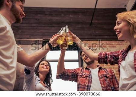 Young people in casual clothes are resting, clanging bottles of drink together, talking and smiling