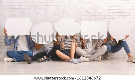 Young people in casual clothes hiding behind speech bubbles, sitting on floor, communication concept, white background Foto stock ©