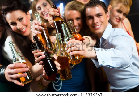 Young people in club or bar drinking beer out of a beer bottle and have fun #113376367