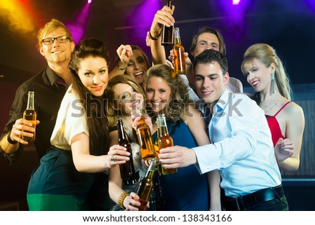 Young people in club or bar drinking beer out of a beer bottle and have fun - stock photo