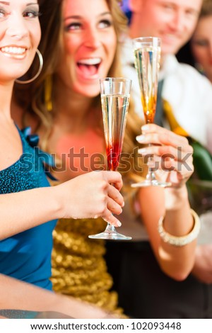 Young people in club or bar drinking champagne and having fun