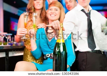 Young people in club or bar drinking champagne and having fun; all are looking into the camera