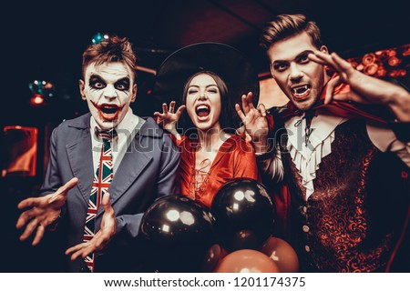 Young People in Costumes Celebrating Halloween. Group of Young Happy Friends Wearing Halloween Costumes having Fun at Party in Nightclub by doing Scary faces. Celebration of Halloween