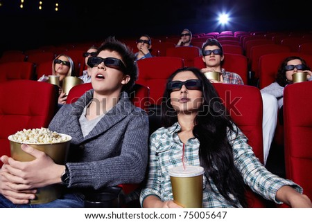 Young people in 3D glasses hard watching a movie at the cinema