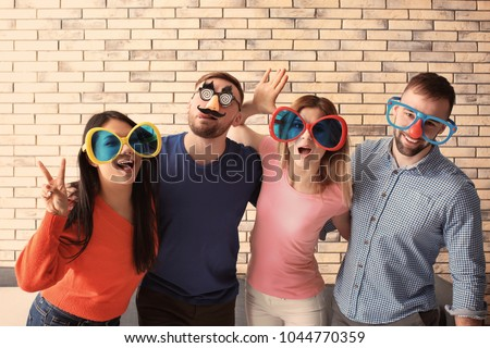 Young people in funny disguise posing on brick wall background. April fool's day celebration Сток-фото ©