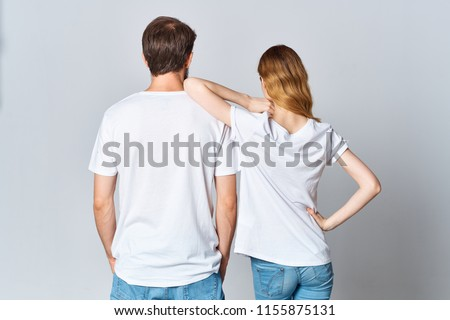 young people in light T-shirts back view