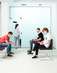 Young people in medical masks, sitting in a queue and waiting for a doctor's appointment in the hospital.