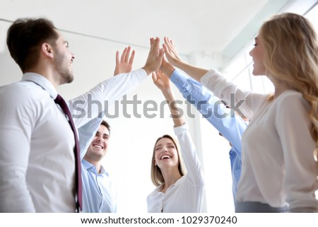 Young people in office wear putting hands together indoors. Unity concept #1029370240