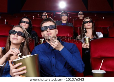 Young people in the cinema in 3D glasses