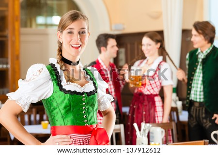 Young people in traditional Bavarian Tracht in restaurant or pub, one woman is standing in front, the group in the background