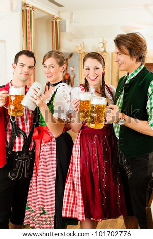 Young people in traditional Bavarian Tracht in restaurant or pub with beer and steins