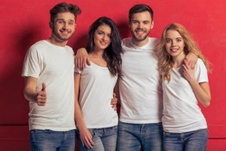 Young people in white t shirts and jeans are looking at camera and smiling, standing against red background