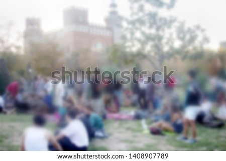 Young people lying on the lawn, fancy place. Strong blur, anonymous people on the streets of Europe
