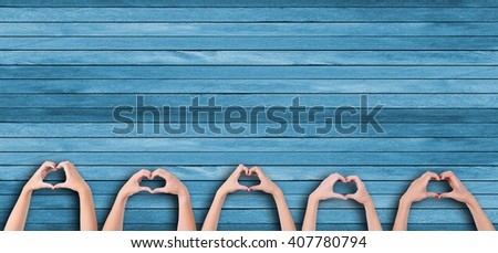 Young people makes hearts using fingers on wooden background - Shutterstock ID 407780794