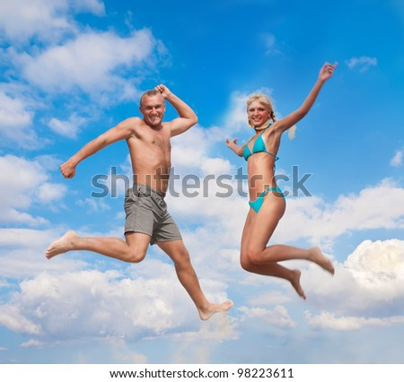young people - man and woman - jumping in the air against a blue sky