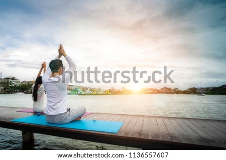Young people meditate on the waterfront on a wooden bridge for good health.