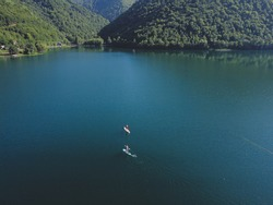 Young people on stand up paddle board on the lake. Aerial drone view of tourists and stand up paddle boarders  on the water at summer. Recreation.
