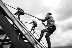 Young people pass the obstacle course. Rise to the obstacle. Teamwork.