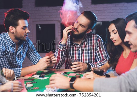 Young people play poker at the table. On the table they have glasses with alcoholic beverages, mobile phones and chips for the game. One of the players is smoking a cigar. #752854201