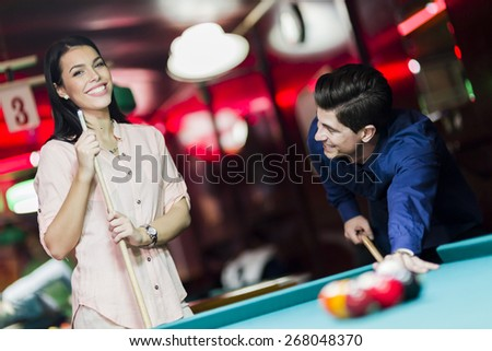 Young people playing billiard in a club pub bar