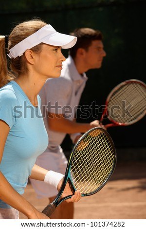 Young people playing tennis, mixed doubles, side view.