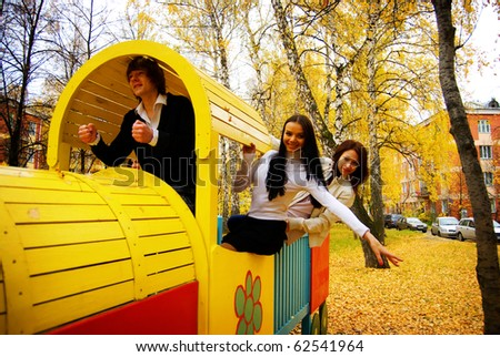 Young people playing the ape on playground in autumn park - stock photo