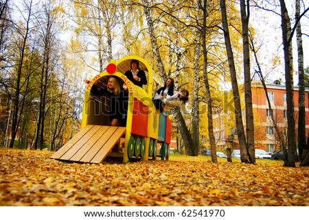 Young people playing the ape on playground in autumn park