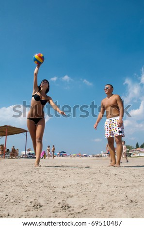 young people playing volleyball on the beach