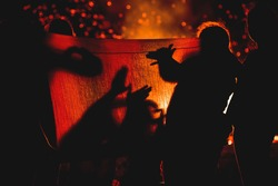 Young people playing with silhouettes and have fun in summer night in front of fire