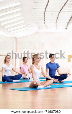 Young people practice yoga in the fitness club