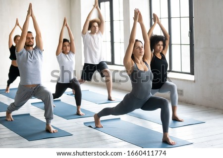 Young people practicing yoga indoor doing Warrior one exercise or Virabhadrasana 1, beautiful slim Caucasian female instructor standing in asana showing teaching diverse girls and guys at group lesson