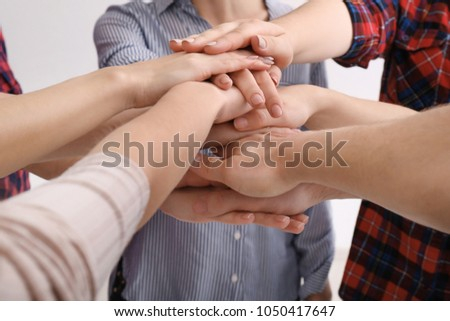 Young people putting hands together as symbol of unity, closeup #1050417647