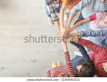 Young people putting hands together indoors. Unity concept #1140440321
