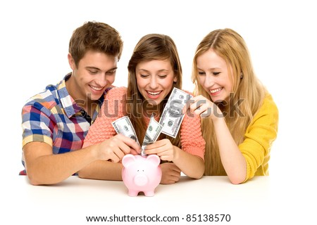 Young people putting money in piggy bank
