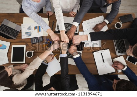 Young people putting their fists together as symbol of unity and achievement, top view. Group of people fist bump assemble together over workplace. Teamwork concept, copy space in middle