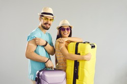 Young people ready for safe summer holiday journey. Studio portrait of happy couple holding travel cases, smiling and showing arms after receiving COVID-19 vaccine. Coronavirus vaccination concept