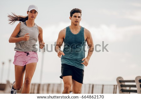 Young people running outdoors. Couple of runners on morning run.