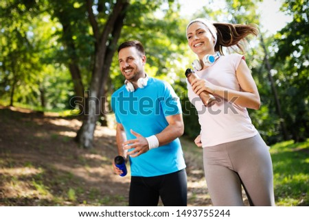Young people running outdoors. Couple or friends of runners exercising in park stock photo