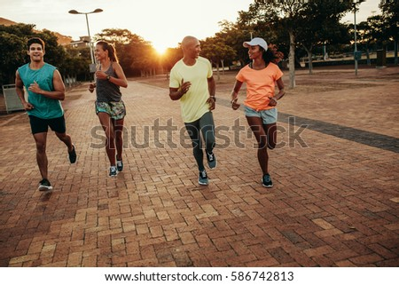 Young people running together at the park. Runners training outdoors in evening. #586742813