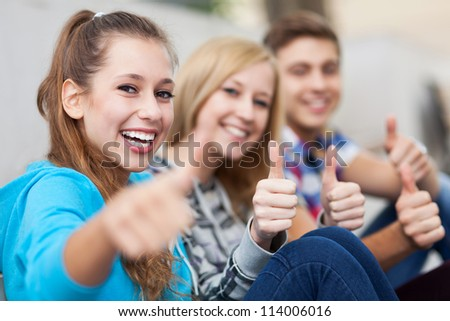 Young people showing thumbs up - stock photo
