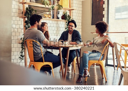 Young people sitting at a cafe table. Group of friends talking in a coffee shop.
