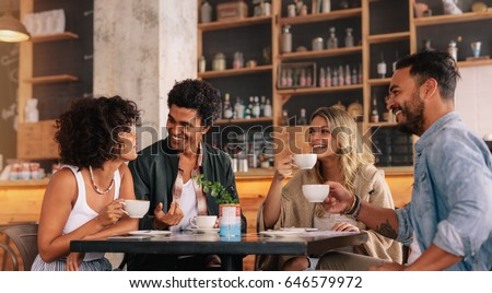 Young people sitting at a coffee shop and talking. Group of friends having coffee together in a cafe.