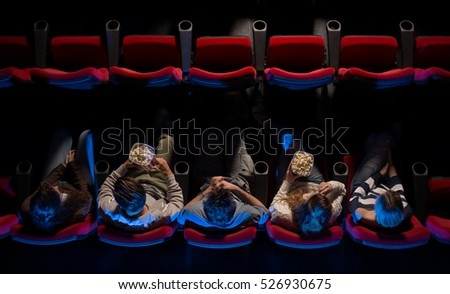 Photo of  Young people sitting at the cinema, watching a movie and eating pop corn, top view